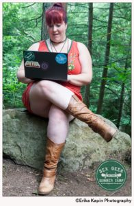 Heather Sitting on a rock in the forrest working on a laptop. They are wearing an orange dress, and light brown cowboy boots
