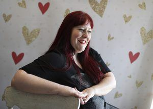 Heather sits sideways behind a while chair, laughing. The background is pink with red and gold hearts.